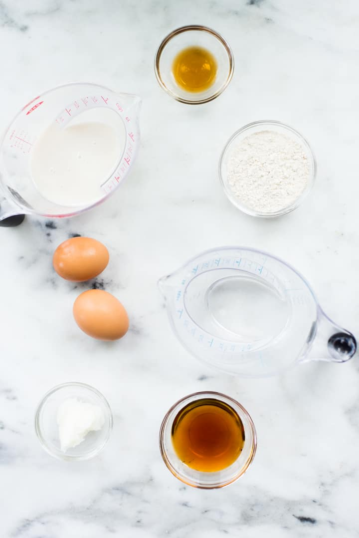 Overhead view of ingredients for Homemade Healthy Crepes, including eggs, unsweetened almond milk, vanilla, maple syrup, whole wheat pastry flour, and coconut oil.