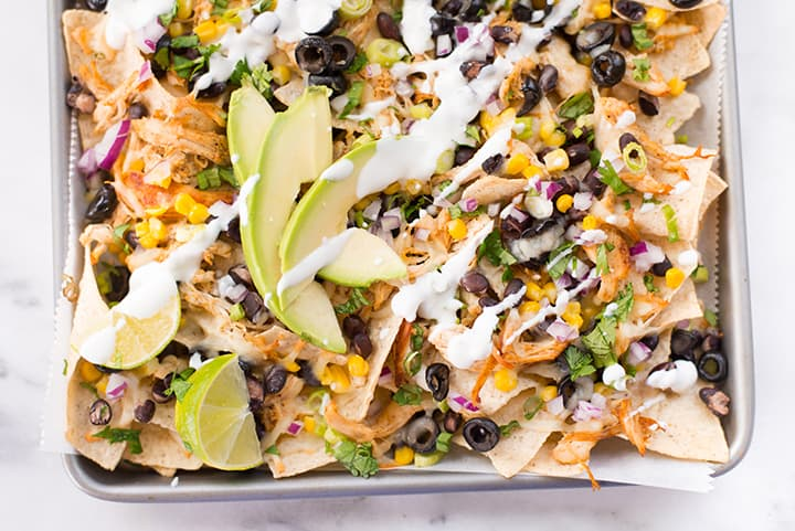 Close up of shredded chicken nachos, topped with final drizzle of greek yogurt, avocado, lime wedges