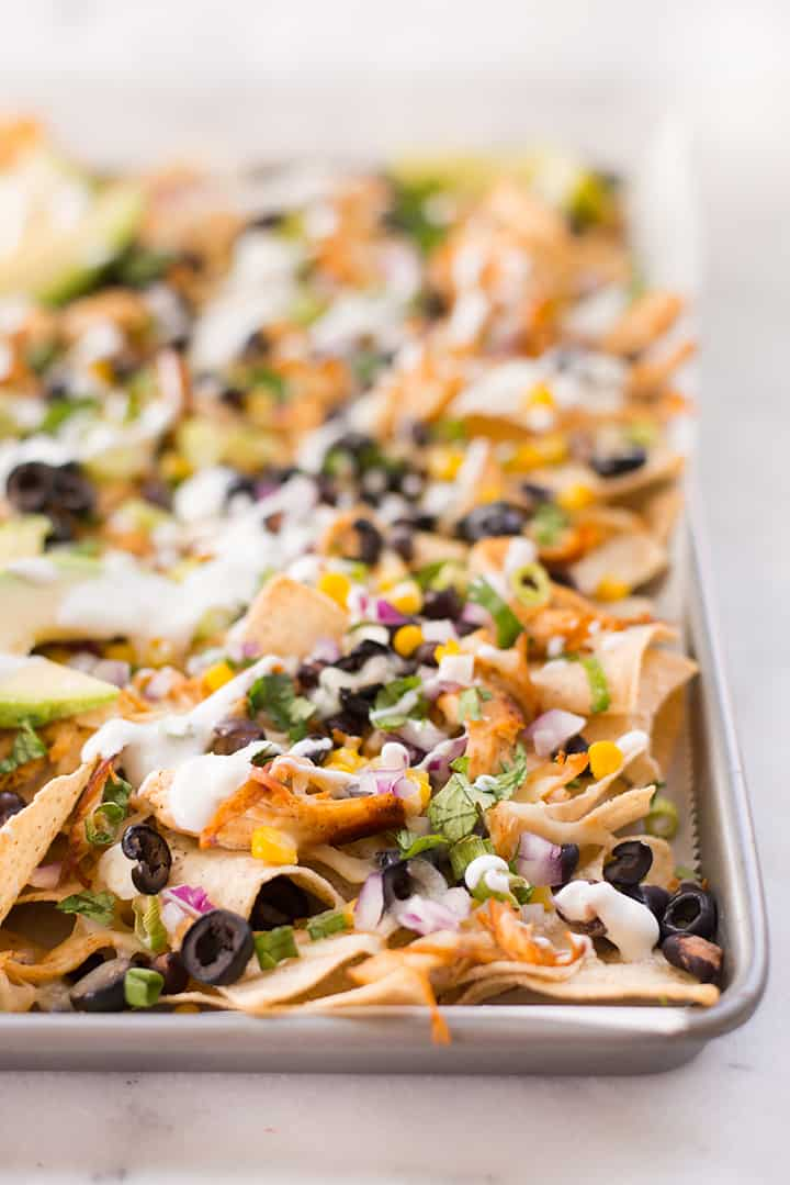 Side view of baking sheet with baked shredded chicken nachos, ready to be enjoyed.