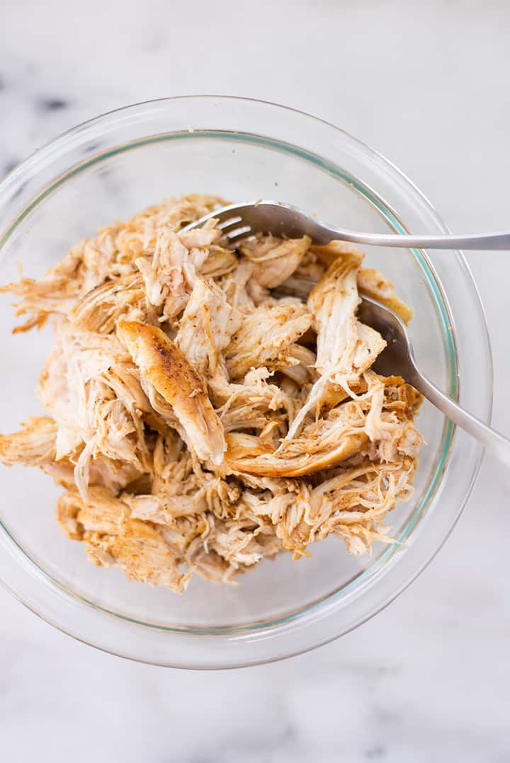 Overhead view of a bowl filled with shredded chicken breast, ready to be used as a topping on the shredded chicken nachos.