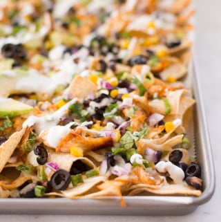 These easy and healthy Shredded Chicken Nachos are a super easy weeknight meal. They take less than 40 minutes from start to finish and use a sheet pan for easy clean-up.