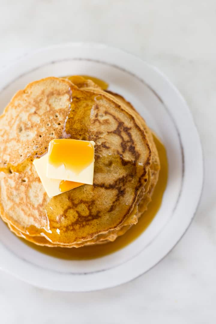 Overhead view looking down on a stack of Healthy Diner Style Pancakes, on a white plate, topped with butter and pure maple syrup.