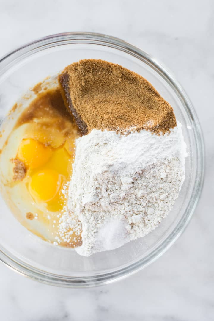 Overhead view of the bowl of dry and wet ingredients for diner style pancakes, including eggs, coconut sugar, and almond flour.