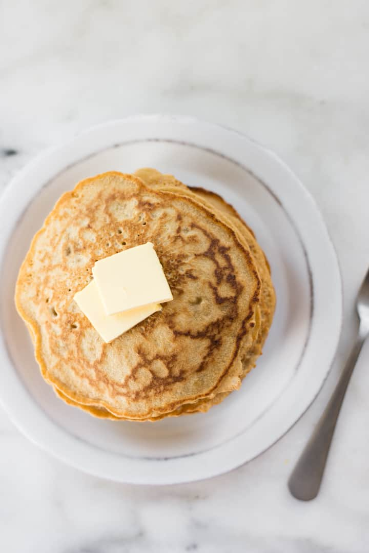 Overhead view of a stack of Healthy Diner Pancakes on a white plate, topped with butter.