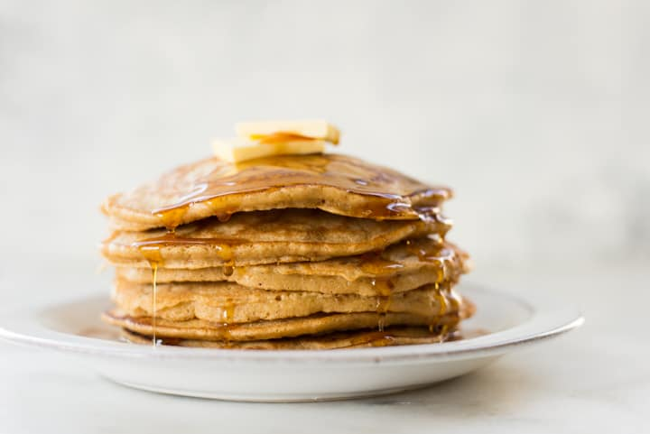 Close up side view of a stack of Healthy Diner Style Pancakes, topped with pure maple syrup and butter, ready to be eaten.
