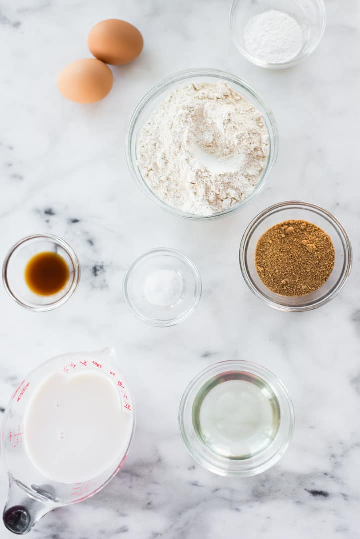 Overhead view of ingredients for Healthy Diner Style Pancakes, including eggs, almond flour, coconut sugar, coconut oil, sea salt, baking powder, and vanilla extract.