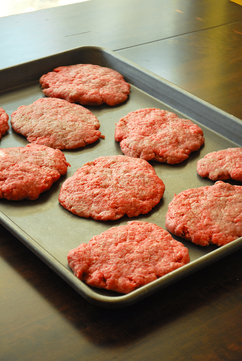 View of My Go-To Best Homemade Burgers, formed and ready to go, placed on a metal baking sheet for carrying to the grill.