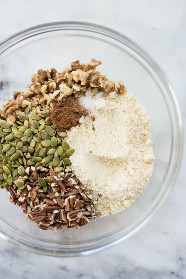 Overhead view of a glass bowl with ingredients for the crumble topping, including almond flour, nuts, pepitas, cinnamon, sea salt, and coconut oil.