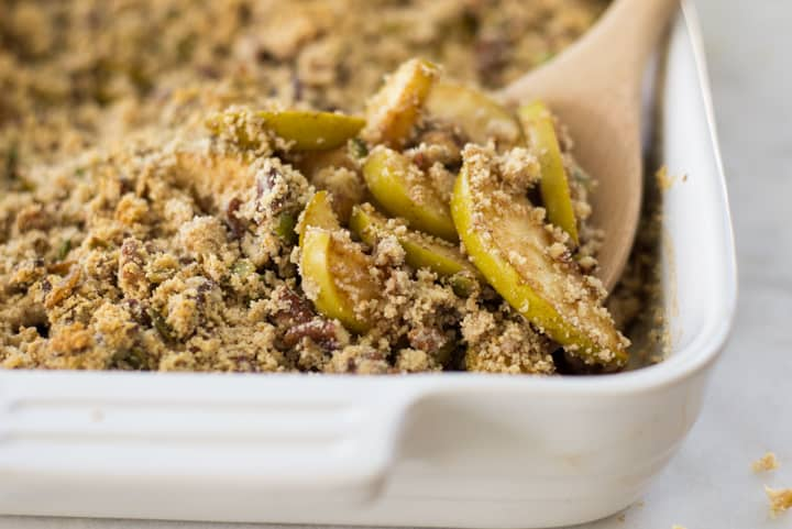 Close up of a white ceramic dish full of baked Healthy Apple Crumble, being served with a wooden serving spoon.