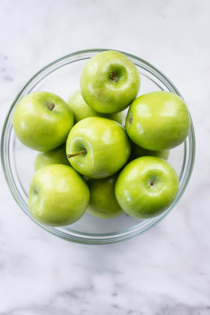 Overhead image of a glass bowl filled with Granny Smith Apples, a good source of dietary fiber.