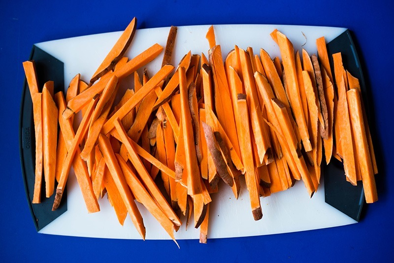 Raw sweet potatoes cut into fry-shaped pieces, ready to be used - showing how to make sweet potato fries.