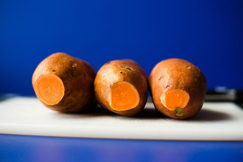 Side angle photo of whole, uncooked sweet potatoes resting on a chopping board, ready to be used for sweet potato fries recipe to show how to make sweet potato fries.