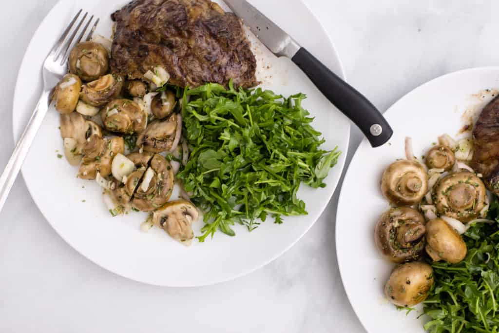 Overhead image of white plates with marinated mushrooms, steak, and greens; a fork and knife are on one plate.