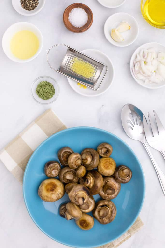 Overhead view of ingredients to make marinated mushrooms, including lemon, oregano, kosher salt, and garlic cloves, with a blue plate of mushrooms nearby.