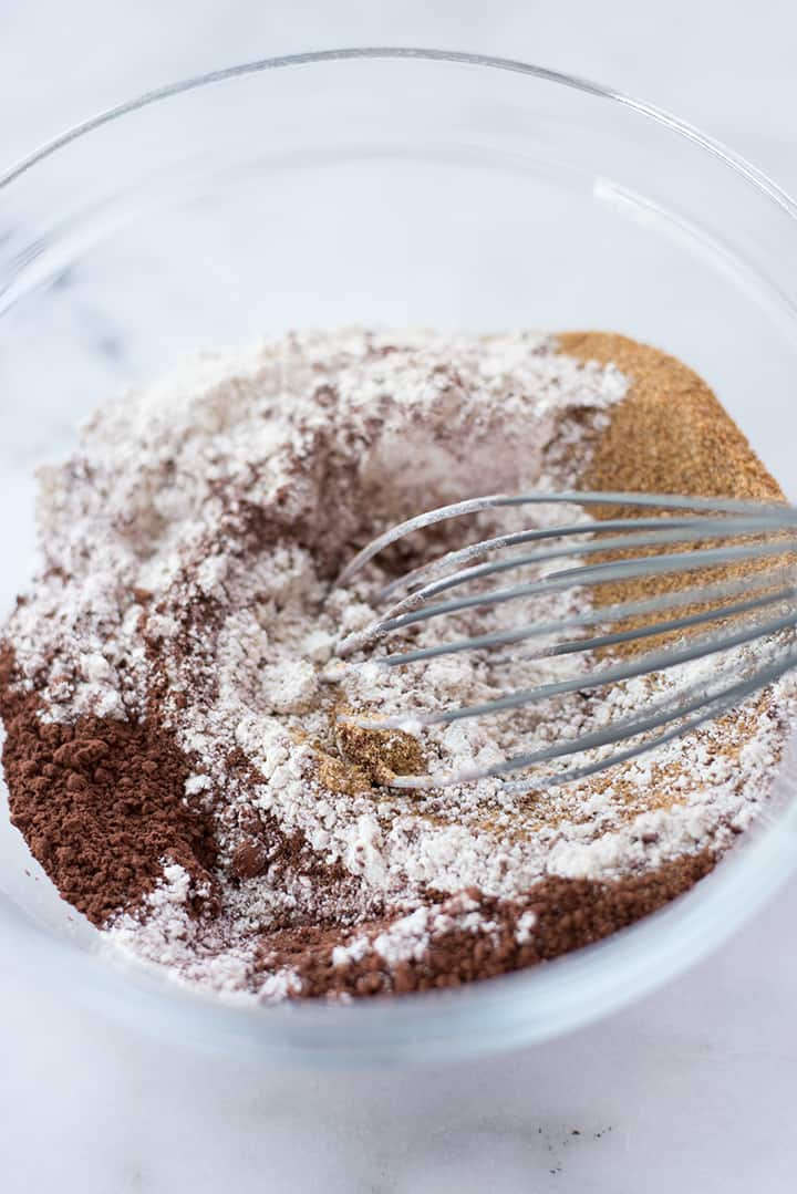 Overhead view of bowl and whisk, mixing together the dry ingredients for Healthy Chocolate Brownies, including dark chocolate cocoa, coconut sugar, and whole wheat flour.