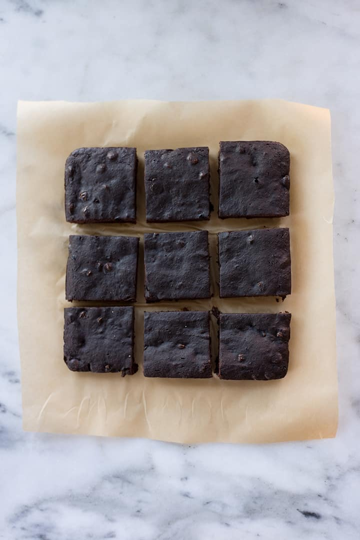 Overhead image of cooked brownies cut into squares, resting on a piece of parchment paper, ready to enjoy.