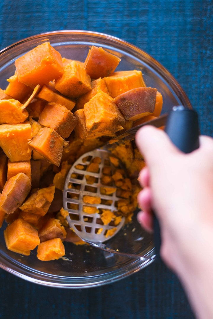 Mixing bowl filled with the steamed sweet potatoes, ground cinnamon, and pure maple syrup, being mashed by hand using a potato masher.