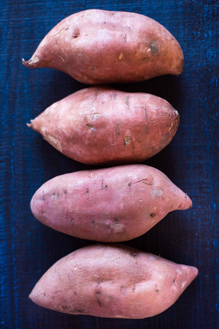 Four sweet potatoes laying in a row, with their skin on. Ready to be diced and steamed, but no need to remove the skin to make the mashed sweet potatoes