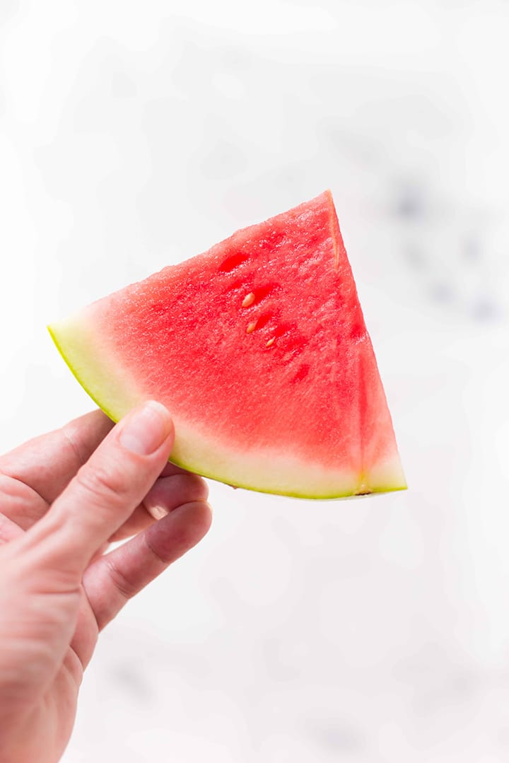 Hand holding a single slice of watermelon, ready to be frozen and turned into watermelon sorbet.