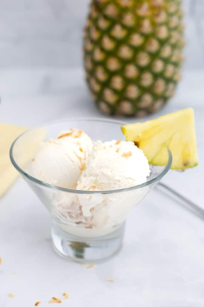 Close up side view of a bowl of pineapple coconut ice cream with a section of pineapple on the bowl side.