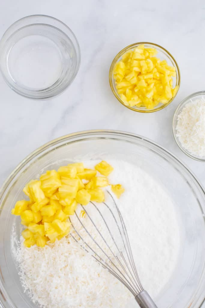Overhead view of a bowl of coconut milk and pineapple chunks being whisked and bowls of pineapple and coconut off to the side.