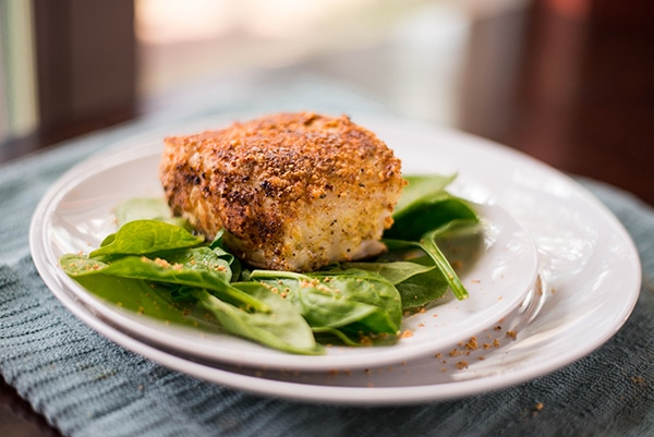 Closeup side view of a white plate with Almond-Crusted Sea Bass on a bed of spinach, ready to eat.