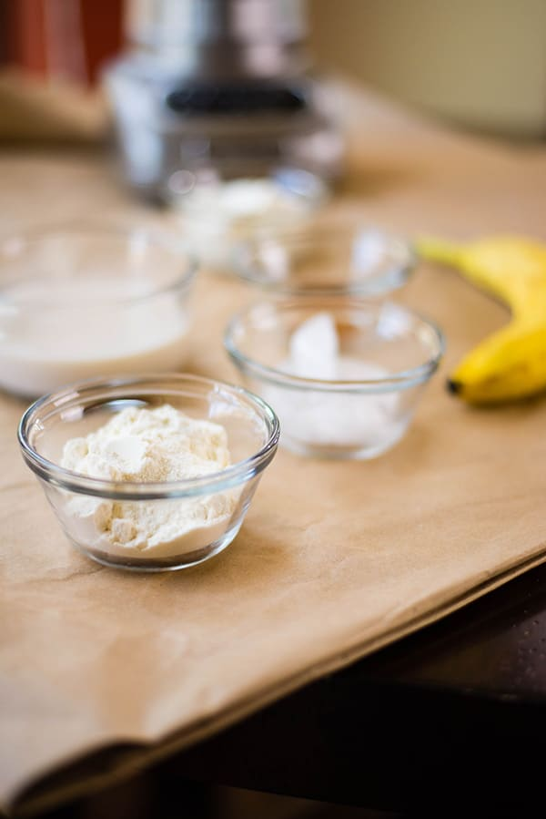 Bowls filled with the ingredients needed to make a banana protein shake