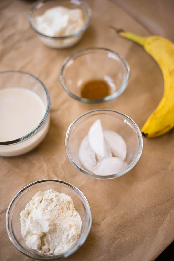 : Vanilla protein powder, a frozen banana, almond milk, and ground cinnamon used to make a banana protein shake