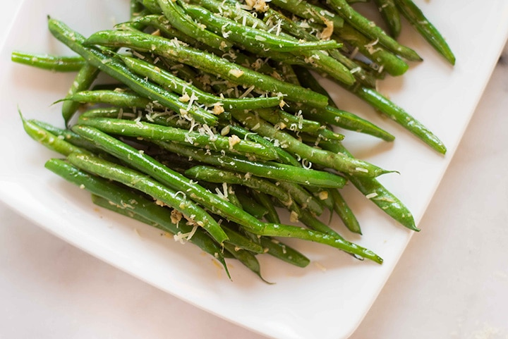 Horizontal image of the garlic parmesan green beans. Close up to show texture and grated parmesan.