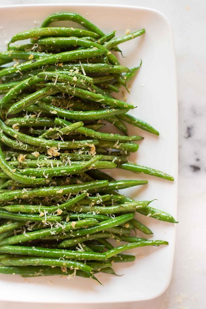 Garlic parmesan green beans lined up on a white plate, garnished with grated parmesan cheese, and ready to eat.