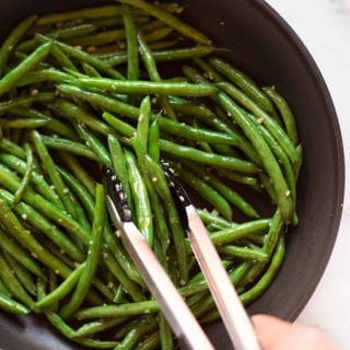 Skillet filled with olive oil, fresh green beans, minced garlic, sea salt, and pepper, sautéing the green beans for the garlic parmesan green beans.