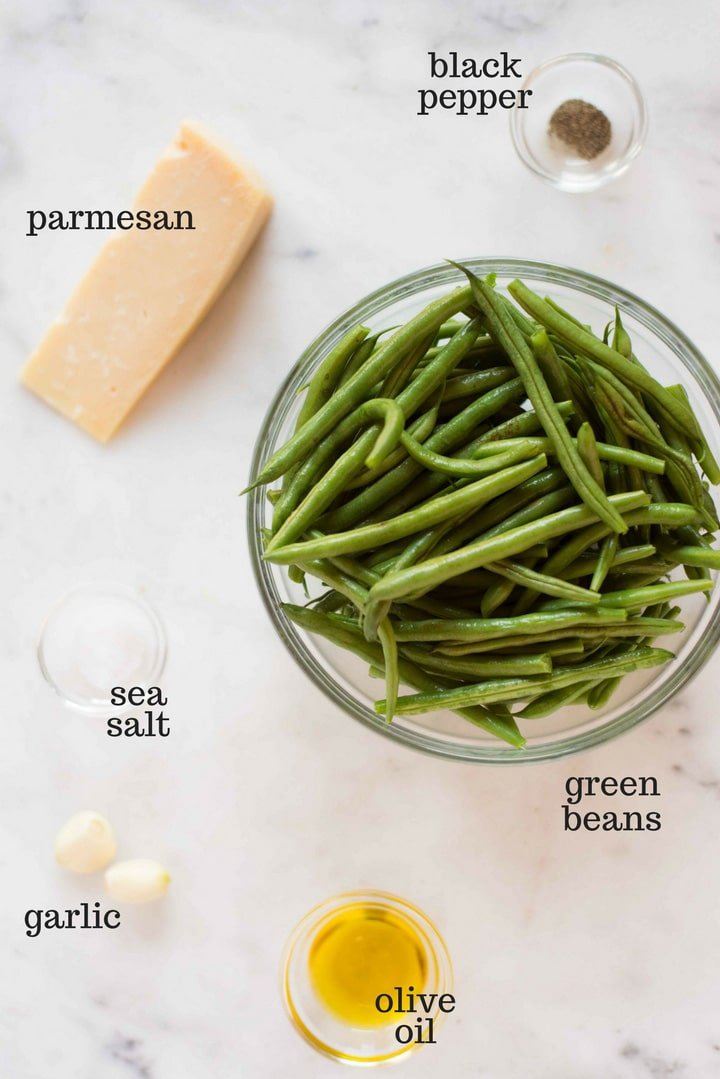 Separate ingredients ready to be used for the garlic parmesan green beans, including the fresh green beans, olive oil, sea salt, black pepper, garlic, and parmesan cheese.