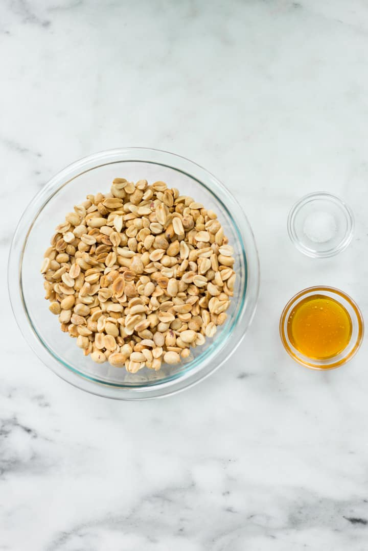 Overhead view of ingredients for Honey Roasted Peanut Butter, which are sea salt, peanuts, and raw honey.