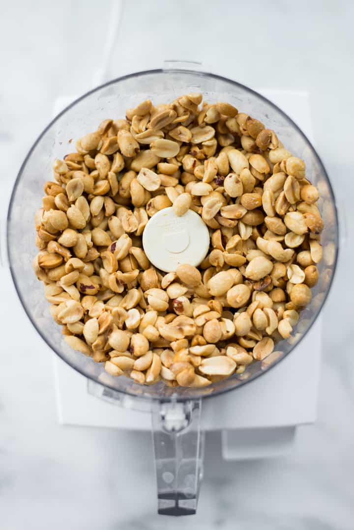 Overhead image of roasted peanuts in the food processor, ready to make Honey Roasted Peanut Butter.
