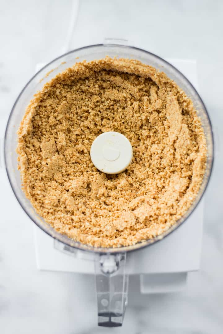 Overhead view of the food processor full of peanuts partially processed in preparation for Honey Roasted Peanut Butter.