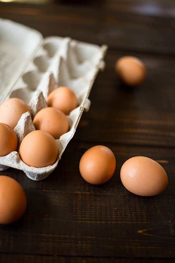 Close up view of a carton of eggs, with 5 in the carton and 4 laying on the counter beside the carton.