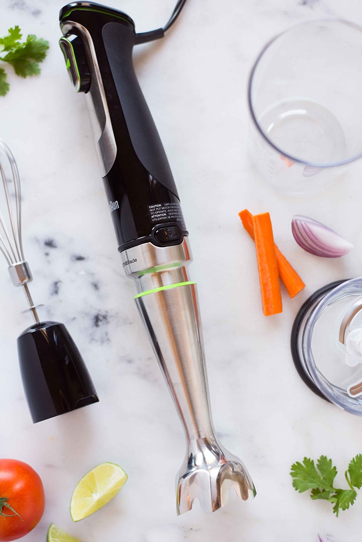 Overhead image of an immersion blender and several attachments, including a whisk and a chopper.