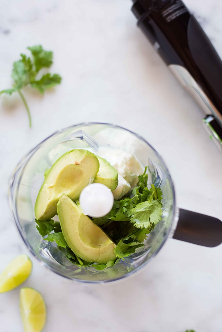 Jug blender attachment of the immersion blender that is being used to make an avocado cilantro lime dressing.