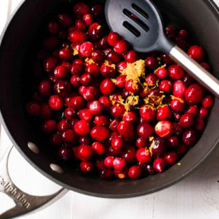 Overhead view of all four ingredients, the fresh cranberries, orange zest, raw honey, and orange juice, are in a sauce pan to be cooked down to make the best homemade cranberry sauce.