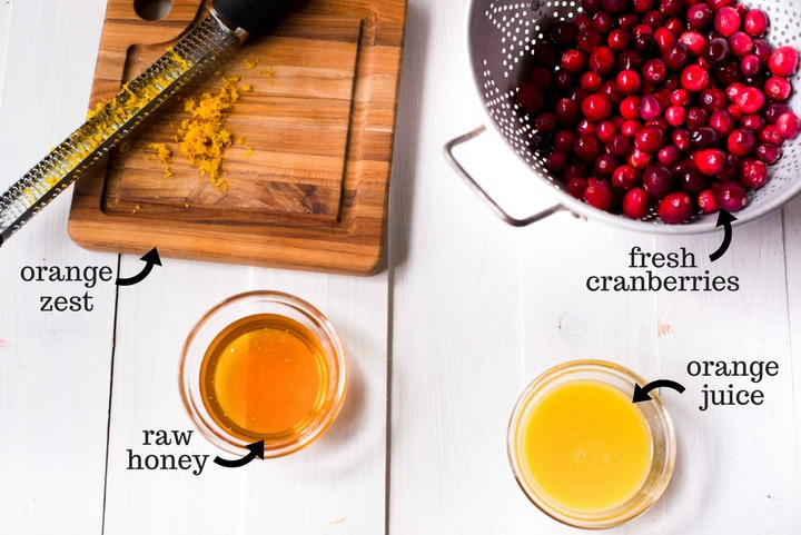 The four ingredients necessary to make the best homemade cranberry sauce. Pictured are fresh orange zest, orange juice, fresh cranberries, and raw honey.