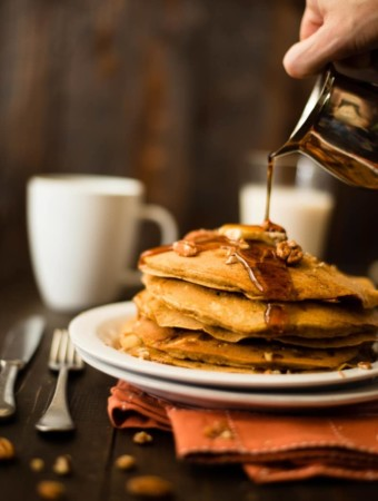 View of pure maple syrup being poured over a stack of healthy pumpkin pancakes