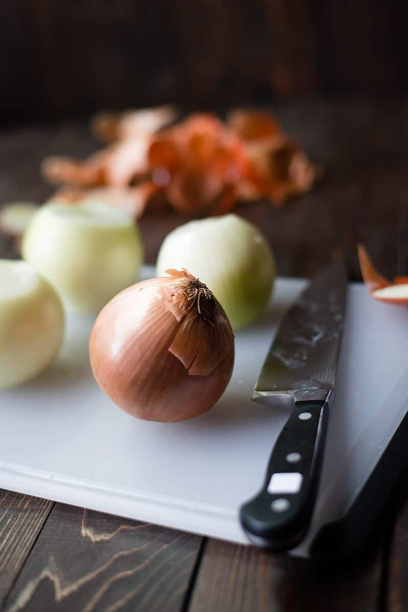 Close up side view of 4 onions on a cutting board, 3 of them peeled for French Onion Soup.