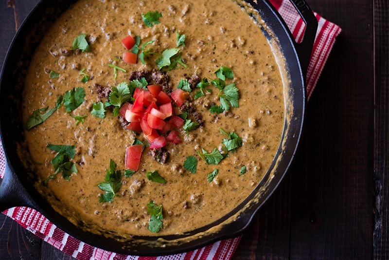 Closeup overhead view of Queso Dip With Ground Beef, garnished with cilantro and diced tomato.