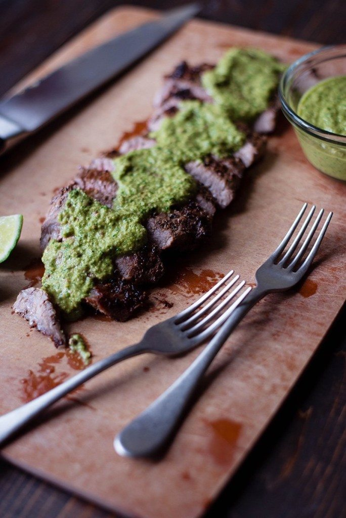Overhead view of Flank Steak With Chimichurri Sauce, ready to serve with extra sauce in a bowl on the side.