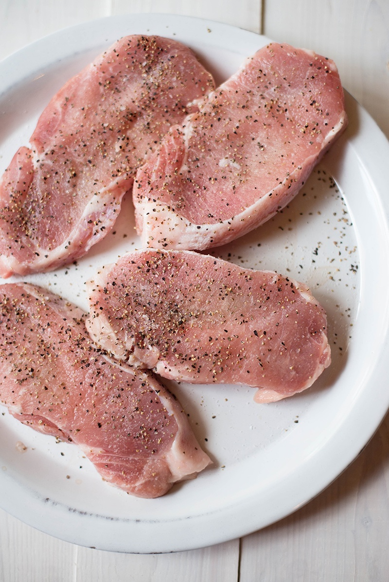 Raw pork chops, seasoned with sea salt and freshly ground pepper and ready to be used for garlic roasted pork chops dish