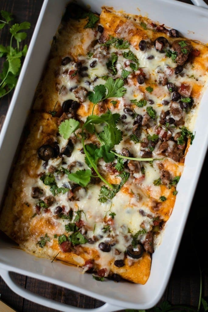 Overhead view of Ground Beef Enchiladas including beef, enchilada sauce, and cilantro, placed in a white casserole dish, ready to serve.