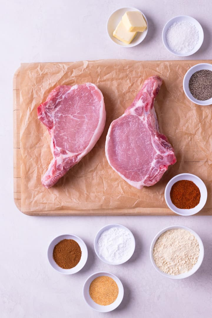 Overhead image of the ingredients for Best Juicy Pork Chops, including cayenne pepper, paprika, sea salt, pepper, bone-in pork chops, and organic butter.