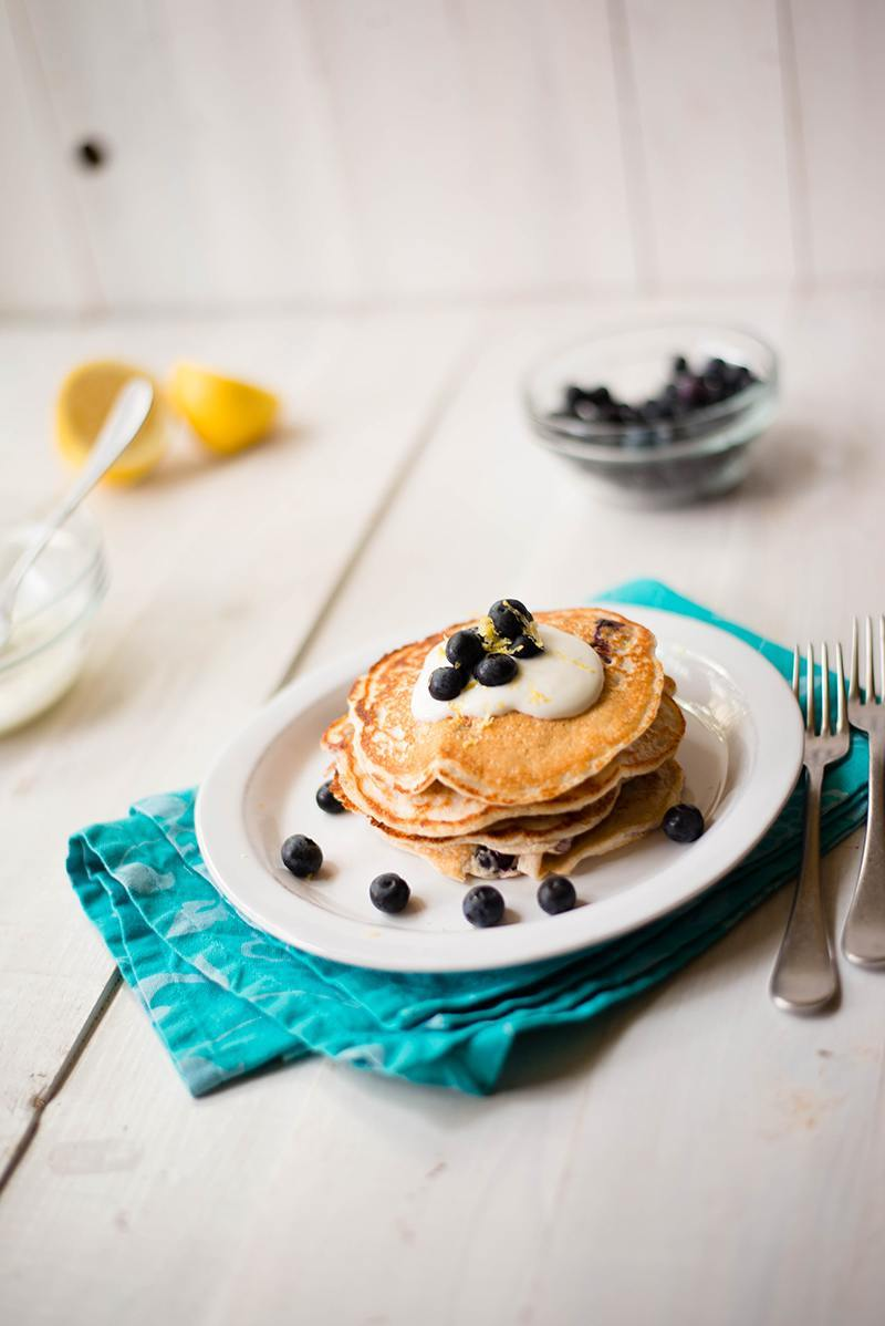 Side angle photo of lemon blueberry high protein pancakes topped with lemon yogurt sauce and garnished with fresh blueberries and lemon zest