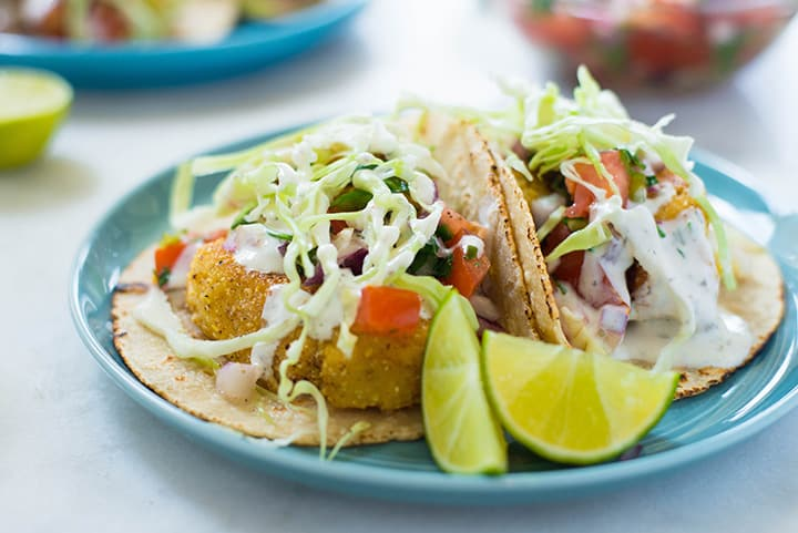 Baja style fish tacos plated and served with fresh lime wedges, homemade pico de Gallo sauce, creamy white dill sauce, and thinly sliced cabbage.