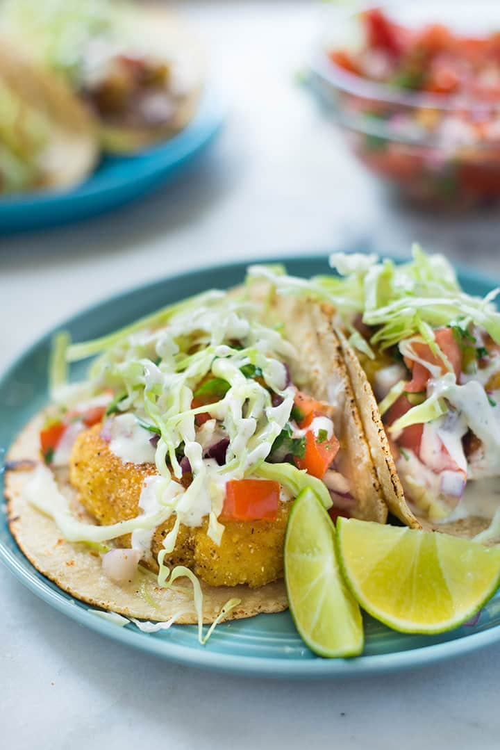 Side angle photo of baja style fish tacos made with homemade corn tortillas and served with fresh lime wedges, and thin slices of cabbage